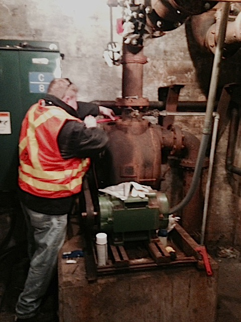 MBTA Outside Machinist Dave Fetherston working on a pump inside the tunnel system.