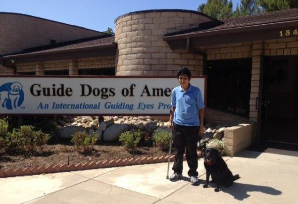 Faith, a 10-year-old guide dog, stands with her recipient Christian at the Guide Dogs of America facility in Sylmar, CA. Christian made the difficult decision to retire Faith after her eight years of service.