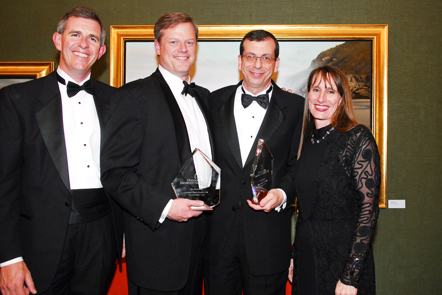 "Charlie Baker receiving his ""Outsourcing Excellence Award"" for sending jobs from Massachusetts to India."
